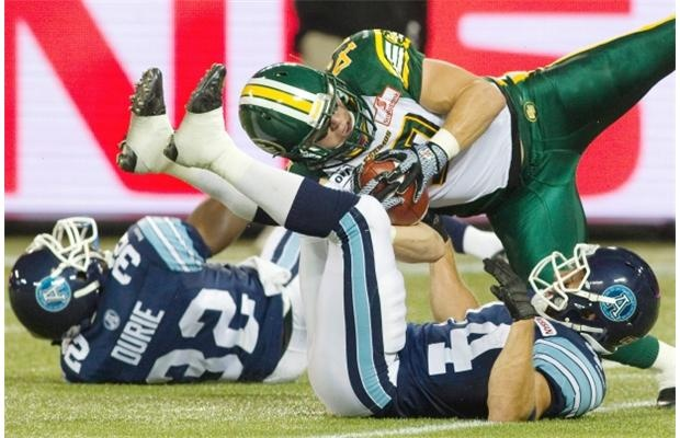 Edmonton Eskimos linebacker J.C Sherritt intercepts a pass from Toronto Argonauts quarterback Ricky Ray as Argos Andre Durie and Chad Kackert, right, lie on the turf at Rogers Centre in Toronto on Aug. 27, 2012.