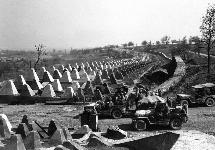 Men of the American 7th Army pour through a breach in the Siegfried Line defenses, on their way to Karlsruhe, Germany on March 27, 1945.