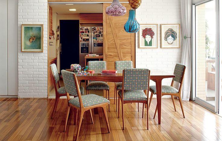 A sala de jantar tem móveis dos anos 1950, garimpados em feiras de antiguidades. Na parede de tijolos aparentes, a porta de correr leva à cozinha. Apesar de ser um apartamento, a decoração feita pela arquiteta Gabriela Marques lembra uma casa