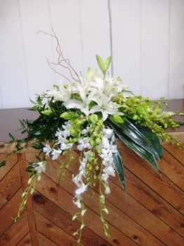 A beautiful white casket spray  by Coleman Florist Inc