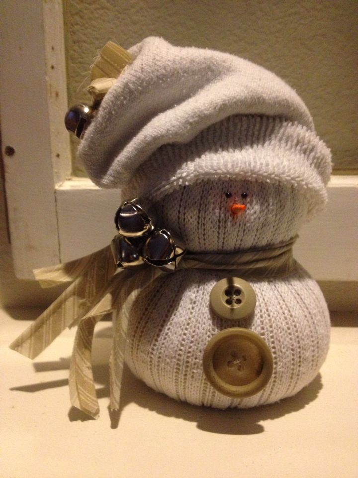 Crew sock snowman stuffed with rice. Bottom sock becomes hat and ribbons, bells, buttons, a BBQ skewer, and push pins to decorate.
