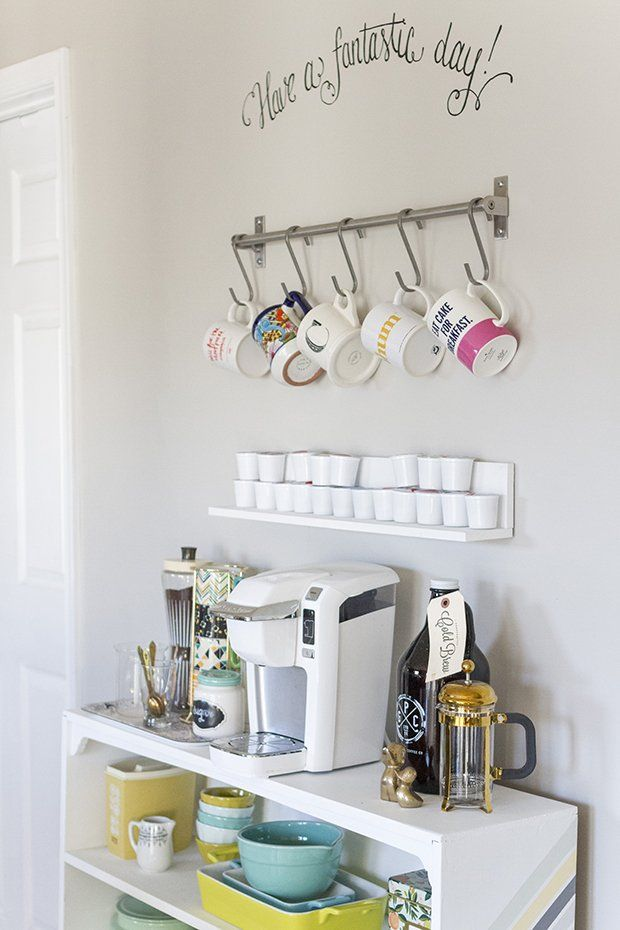 Keeping space cohesive w/ colour will keep it from appearing cluttered: Style the coffee bar bookshelf below with all of the necessary accessories — things like a coffee maker, extra coffee grounds or beans, specialty mugs, tea bags, sugar dishes and coffee stirrers or spoons. By keeping the accessories in a unified color palette, you'll create a cohesive and intentional look that doesn't compete with the rest of the space.