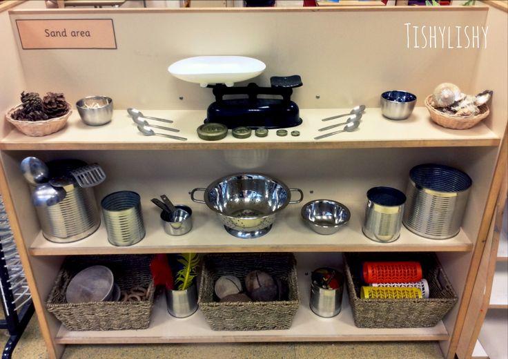 Sand provision. Top shelf; shells, pine cones, matchsticks, tea spoons, scales and gems. Middle shelf; utensils, measuring spoons, colander, bowls, tins. Bottom shelf; wooden bowls, feathers, coconut shells, sticks, coloured spools.