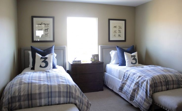 Shared boys' bedroom features twin upholstered headboards with silver nailhead trim accented with white and blue plaid bedding and numbered pillows flanking shared nightstand as well as nailhead ottomans at foot of bed.