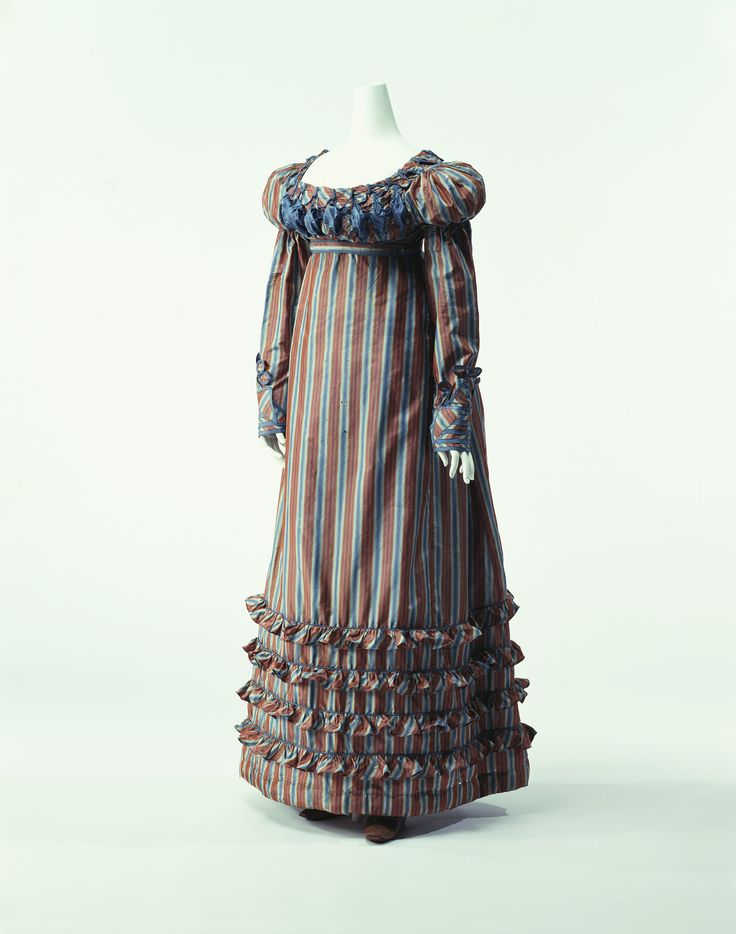 In this period, the use of colors was revived after the dominance of white that had begun in the early 19th century. This dress features inwoven stripes with a strong color combination of brown and blue. The waistline is still high, and the stripes emphasize the vertical lines. A pad is inserted at the center of the back to produce a beautiful back line floating down from the high waist.