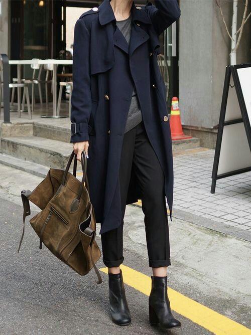 紺のトレンチコートをゆるっと着るとお洒落。ニット×クロップドパンツ×ショートブーツでベーシックな着こなしにバッグも大きくゆるく。カッコイイ。