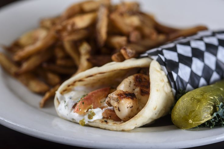 Chicken Souvlaki Pita | morsels of marinated chicken wrapped in a pita with onions, feta, tomatoes & our homemade tzatziki sauce. Served with french fries.