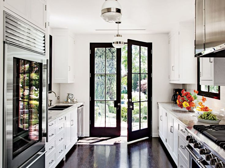A dramatic black door and windowpanes draw the eye in a kitchen that Madeline Stuart designed for a 1950s dwelling in Los Angeles.