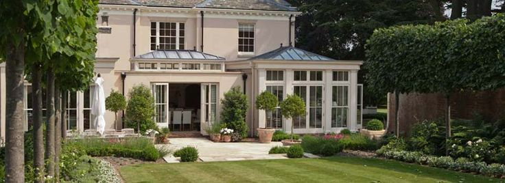 Orangery with full length panels and clerestory and sash window design. Side kitchen area extension incorporates solid walls and a roof lantern with a lead roof. Painted in