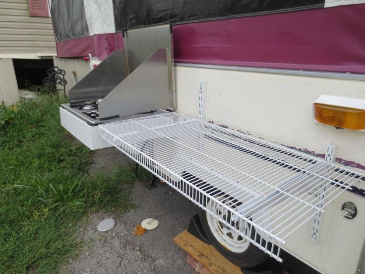 Removable shelf on outside of the camper so you don't have to pack a table. A shelf and grill to cook on and the picnic table to eat on makes it less to pack.
