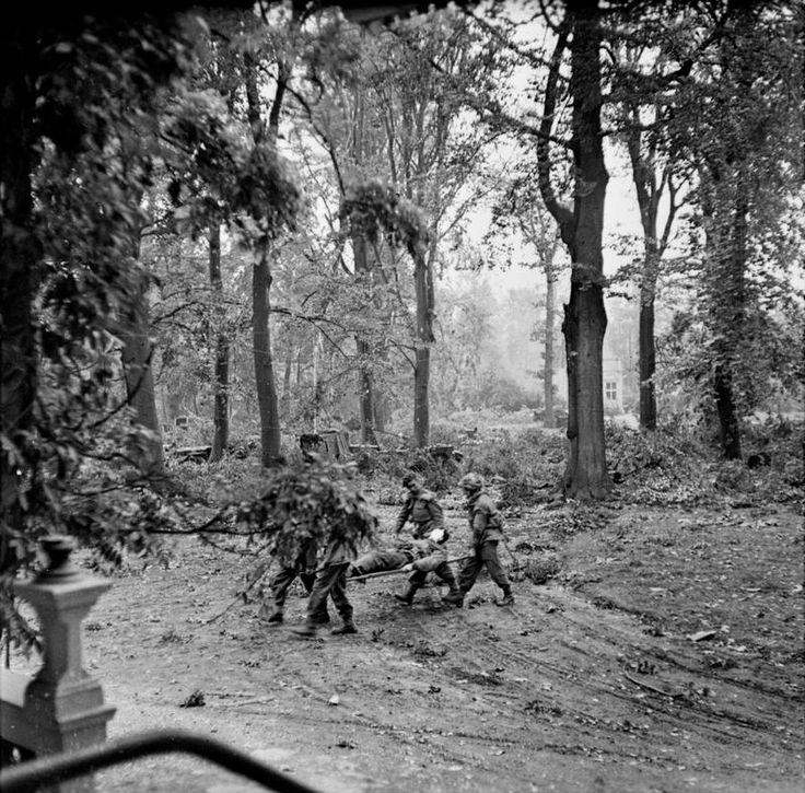A wounded man being carried away from the Divisional Administration Area by stretcher (note the stocks of ammunition and fuel dumped in the background) at Oosterbeek.