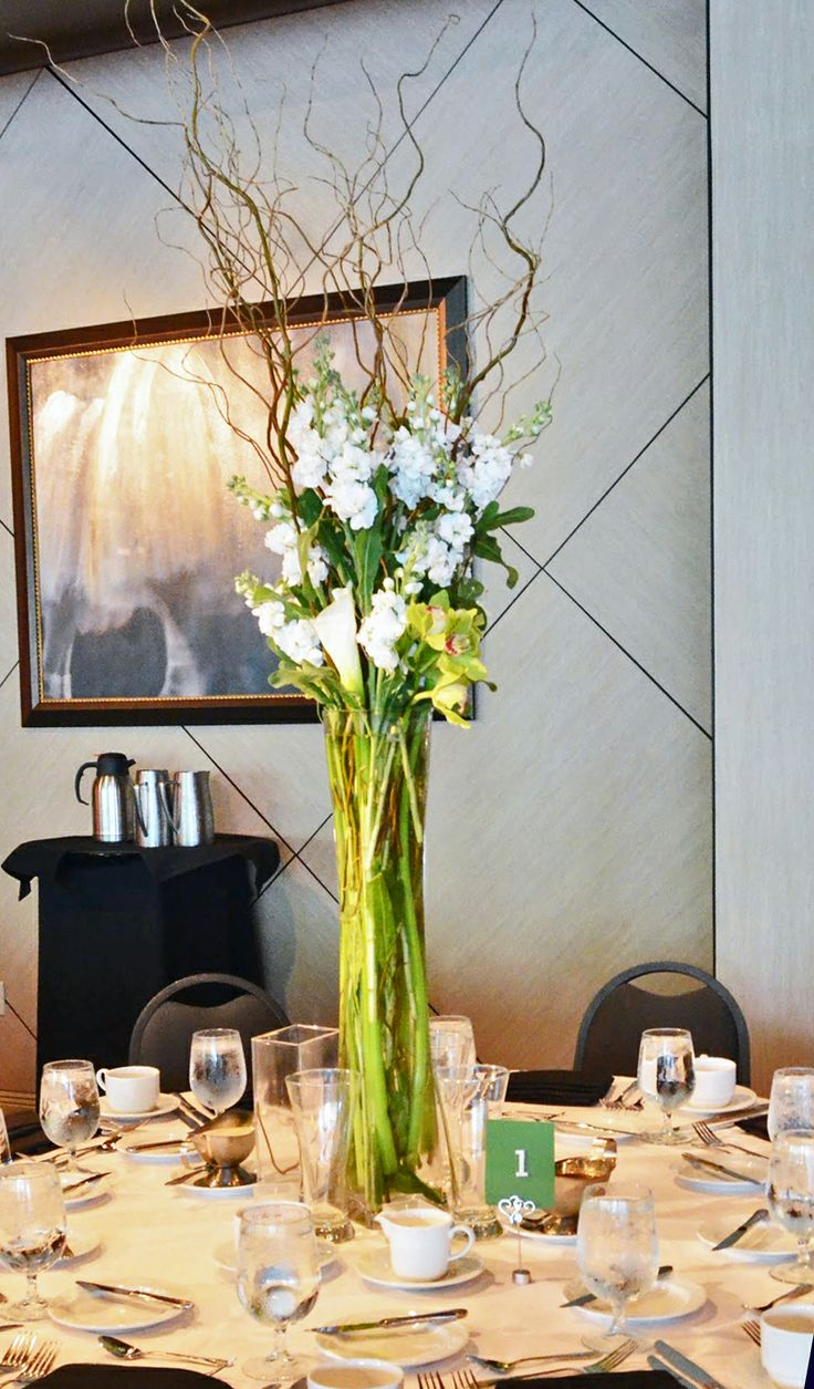 Tall white and green centerpiece contains stock