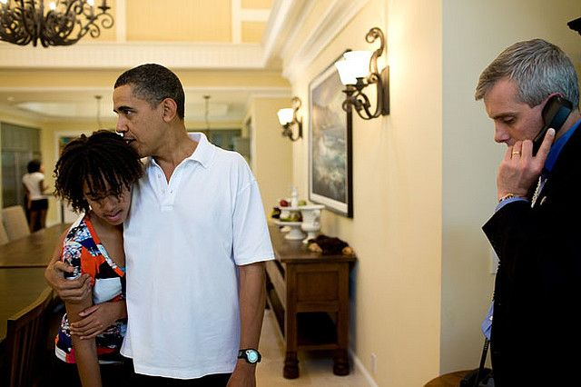 "Dec. 29, 2009 ""I thought this was an interesting juxtaposition between his role as a father, and his role as Commander in Chief. On vacation in Hawaii, here he is hugging his daughter Malia while NSC chief of staff Denis McDonough waits to connect him on the latest conference call following the attempted Christmas Day terrorist attack."" (Official White House photo by Pete Souza)  This official White House photograph is being made available only for publication by news organizations and/or…"