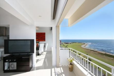 Cape Town apartment - a dining room and kitchen area looking out onto the spectacular ocean view.