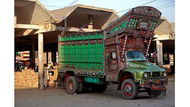 Trabajadores descargan fruta de un camión decorado en el mercado mayorista de Faisalabad