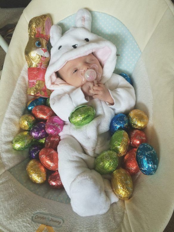 Baby in bunny outfit with lots of eggs.