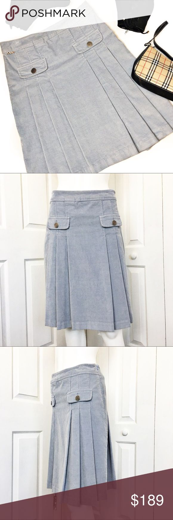 """Burberry Pleated Corduroy Skirt Make a statement in this authentic Burberry corduroy Skirt.  Light blue in color.  Features two false pockets on the front with Burberry embossed button and side zip closure.  Skirt is in pristine condition.  Fully lined.  Care tag was cut but this is dry clean only.  Purchased at the Burberry store at the Tampa mall.  Material tag has been listed.   Measurements laid flat:  Waist:  16"""" Hip:  19"""" Length:  23"""" *Measurements are approximate. Burberry Skirts"""
