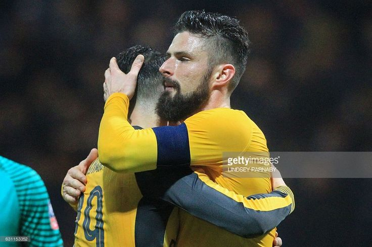 Arsenal's French striker Olivier Giroud (R) embraces Arsenal's Swiss midfielder Granit Xhaka on the pitch after the English FA Cup third round football match between Preston North End and Arsenal at Deepdale in north west England on January 7, 2017. Arsenal won the game 2-1. / AFP / Lindsey PARNABY / RESTRICTED TO EDITORIAL USE. No use with unauthorized audio, video, data, fixture lists, club/league logos or 'live' services. Online in-match use limited to 75 images, no video emulation. No…
