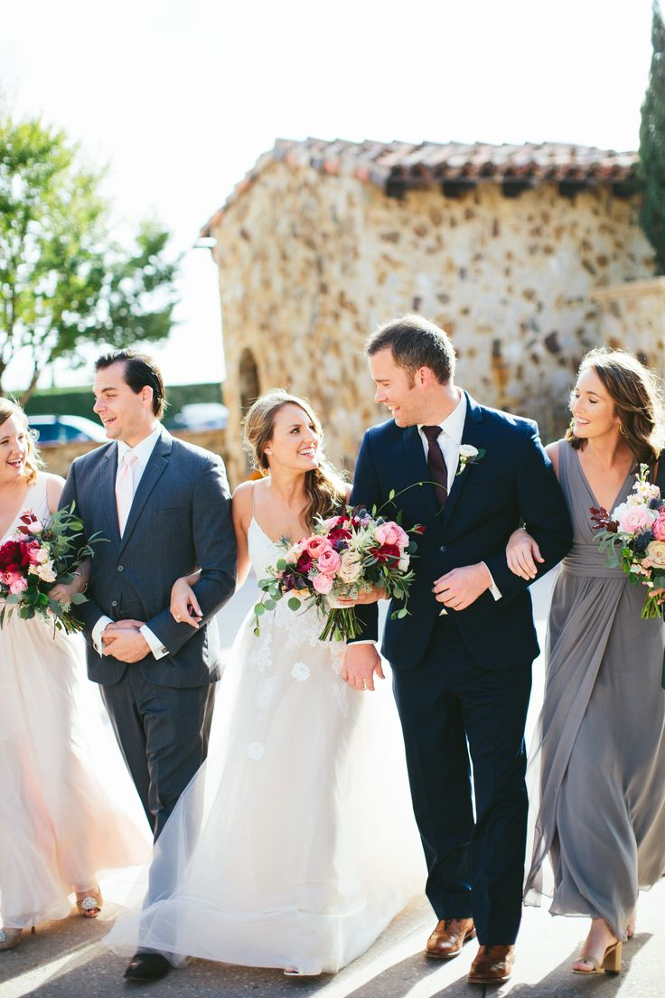 bride and her groom in a navy suit go arm in arm to the reception with their wedding party. the loose and organic bouquets of burgundy, pink, peach, blush and white are a nod to the autumn season.