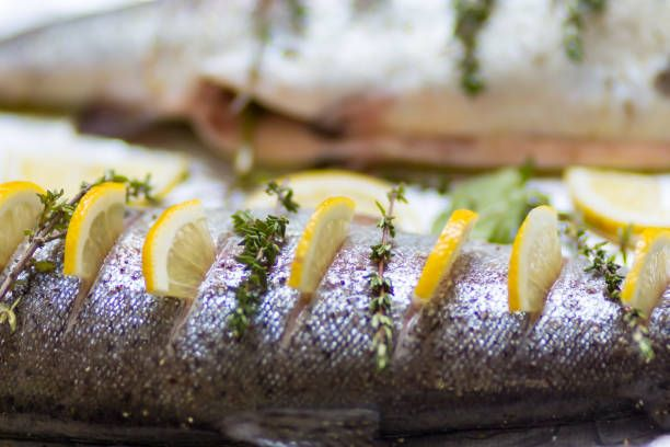 two river fish trout on baking tray stuffed with lemon wedges and a
