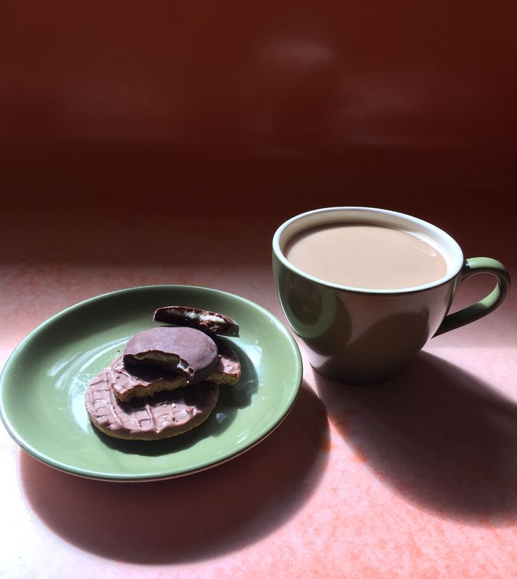 Crown Lynn cup and plate with chocolate biscuits.