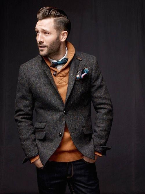 Comprar ropa de este look: https://lookastic.es/moda-hombre/looks/blazer-jersey-con-cuello-chal-camisa-de-vestir-vaqueros-corbatin-panuelo-de-bolsillo/6501 — Corbatín Azul Marino — Camisa de Vestir Blanca — Jersey con Cuello Chal Tabaco — Vaqueros Negros — Pañuelo de Bolsillo Estampado Azul — Blazer de Lana Gris Oscuro