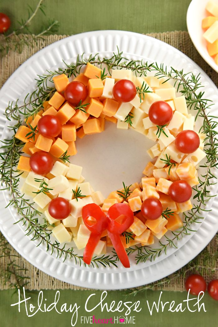 Holiday Cheese Wreath ~ this easy and festive Christmas party appetizer is made by arranging cubes of cheese in a ring, accenting with cherry tomatoes and a garland of rosemary, and finishing off with a bell pepper bow! | FIveHeartHome.com: