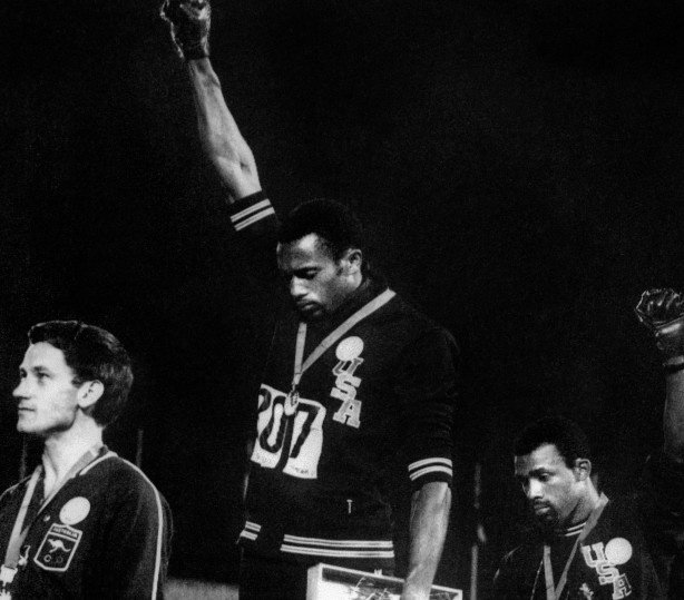 """1960s Australian sprinter Peter Norman (left) stands on the podium next to Americans Tommie Smith and John Carlos as they raise their gloved fists in an iconic salute during the national anthem to express their opposition to racism in the USA.  Norman was wearing a badge that read: """"Olympic Project For Human Rights,"""" borrowed from Paul Hoffman a white athlete. """"I believe every man is born equal and should be treated that way,"""" Norman told reporters…"""
