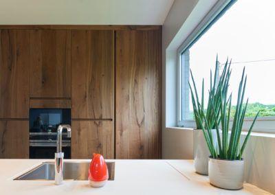 Hedendaagse keuken met een wit, keramisch tablet dat als strak accent dient in dit warm ontwerp. De kastenwand in donkere balkeneik bevat een mooi verlichte koffiecorner. Deze kan volledig verborgen worden achter een hoge inschuifdeur (HaWa Concepta) met een verticale greeplijst.