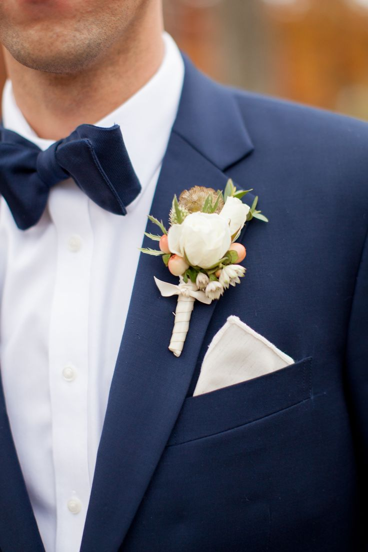 Groom in navy suit and navy bow tie.