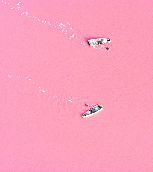 """No Senegal, Lago Retba a água não é azul, mas sim rosa. A alta concentração de sal - em algumas áreas chega mesmo aos 40%, provoca esta mudança de cor. Em entrevista ao Daily Mail, o microbiólogo Michael Danson explica o fenómeno """"A água adquire esta cor por causa da alga Dunaliella Salina, que adora sal. Além disso, produz um pigmento vermelho que absorve e usa a energia da luz solar para criar ainda mais energia, alterando assim a sua cor""""."""