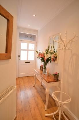 This hallway but with a slightly darker wood, mirror above the table and possibly a shoe rack