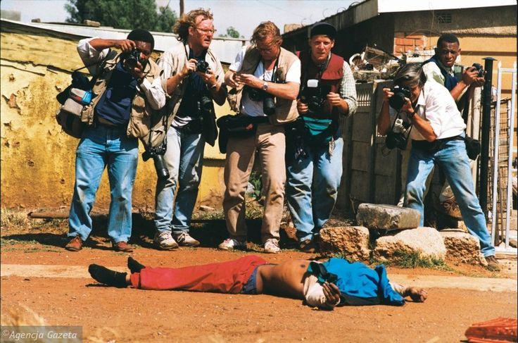 Grupa fotoreporterów stoi nad ciałem zabitego mężczyzny. Fotografują zwłoki jednego z ludzi, którzy zginęli podczas zamieszek przed pierwszymi wolnymi wyborami w RPA w 1994 roku.