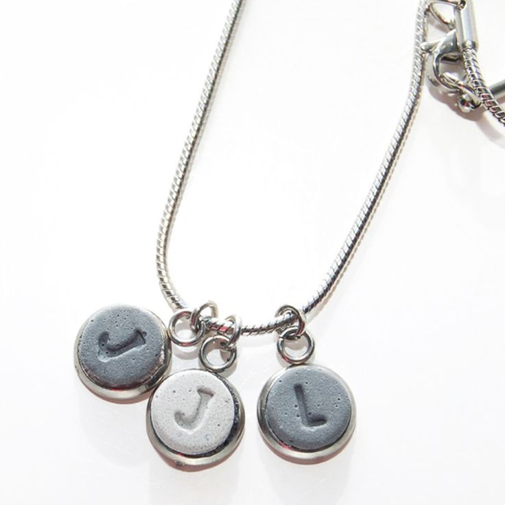 These concrete initial pendants are custom made Hanging from an 18 stainless steel snake chain and set in a stainless steel bezel Please indicate when purchasing the initials and order that you would like them See other listings for 1 and 2 initial pendants Item will arrive in a metal tin