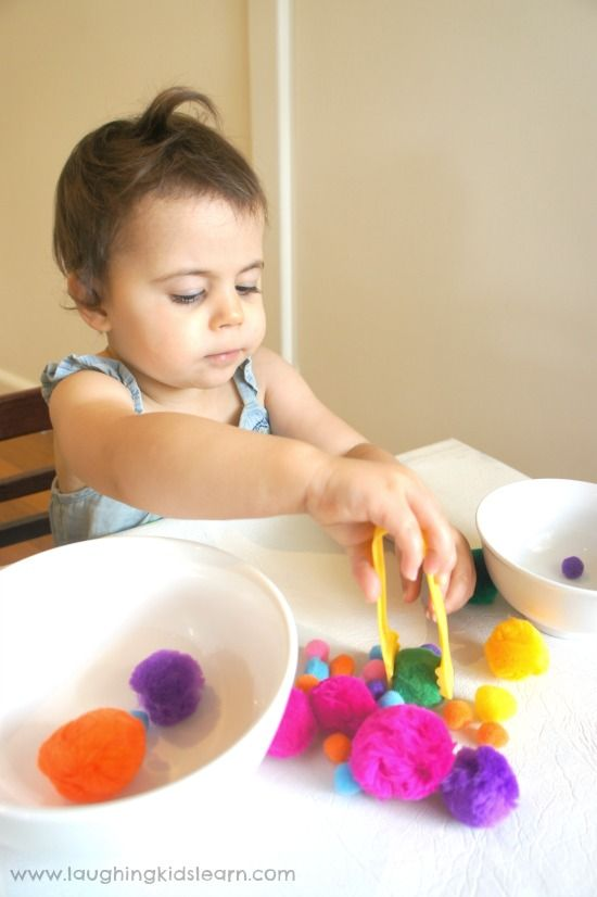 Toddler using tongs in fine motor activity