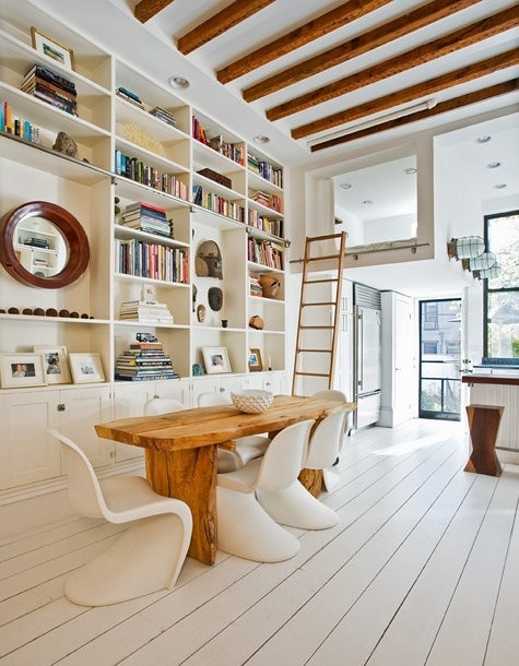 Exposed beams, funky chairs, and well accessorized bookshelfs make this dining room fun for the family!