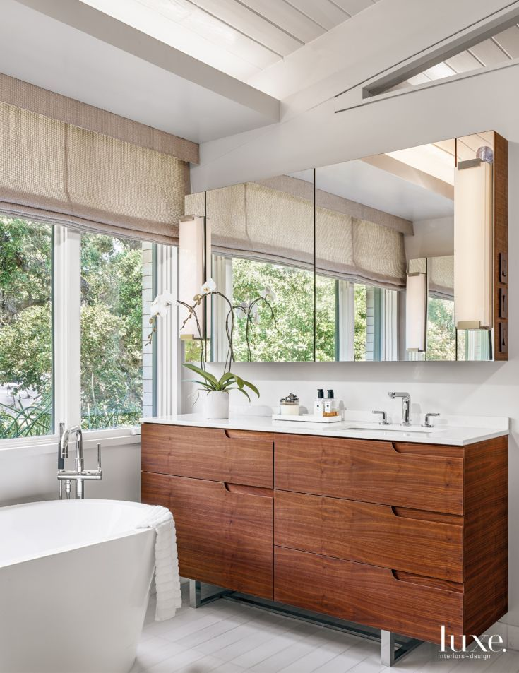 The master bathroom's custom walnut vanity by Honea Woodworks is lit by a Modern Forms sconce; the Kohler sink and Hansgrohe faucet are both from Moore Supply Company. A Signature Hardware tub rests on flooring from Stone Source. Holly Hunt's Great Plains fabric dresses the windows.