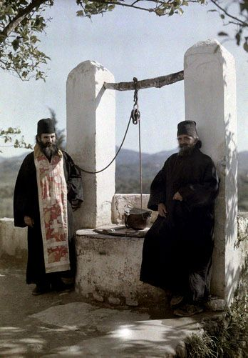 Prior and his monk stand next to well at Europulus monastery, Corfu; 1920's; Images by Maynard Owen Williams / Wilhelm Tobien  Source: National Geographic Stock