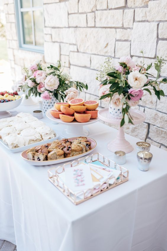 Brunch party with grapefruits, cinnamon buns, donuts, fruit and flowers