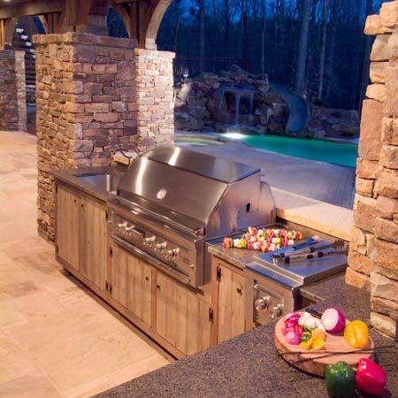 This is what a dream backyard looks like! Outdoor kitchen, pool with a slide and waterfall!!!