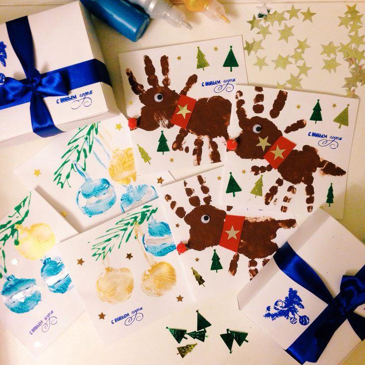 Открытки к новому году. Елочные игрушки сделаны с помощью штампов из картофеля, олени - отпечатки ладоней сына.
