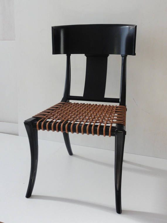 Fascinated and inspired by the Classical furniture of Greece, T.H. Robsjohn-Gibbings based the design for this beautiful Klismos chair on his study of the form found painted on ancient amphora vases. Made of Greek walnut. Back constructed with three pieces of walnut dowelled together.