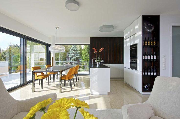 """Lustr italské značky Foscarini dokonale doplňuje střízlivý obývací pokoj. Na míru vyrobená kuchyňská linka pokračuje """"za rohem"""" malým prostorem za posuvnými dveřmi, kde se skrývají úložné prostory, nutné, ale méně pohledné kuchyňské vybavení a veškerý případný """"provozní nepořádek""""."""