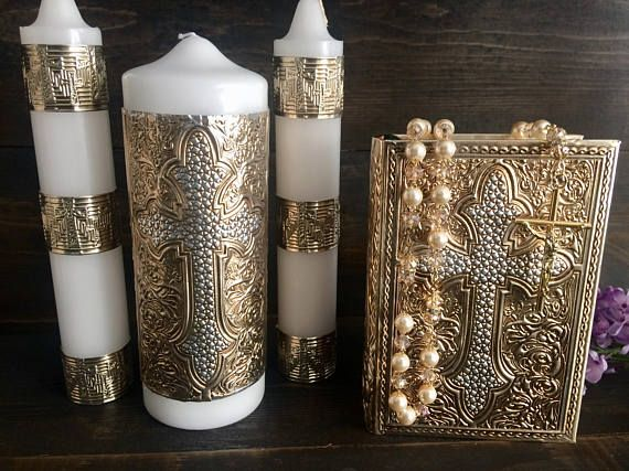 Beautiful unity candle set, wrapped in metal emboss with cross The side candles measure 9x1.5 and the middle candle measures 8x3.8. -Catholic wedding bible in Spanish with matching emboss metal wrapped and full ivory and gold rosary ***no vase needed for the candles to stand**