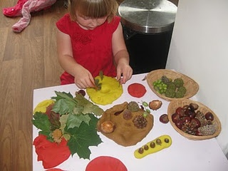 playdough in Autumn colours alongside acorns, fir cones, leaves, twigs, conkers, sweet chestnuts and conker shells