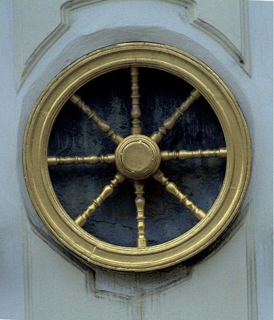 """""""Il vero significato della ruota d'oro""""  Se ai più è nota l'insegna della ruota d'oro, sulla casa """"U zlatého kola"""" (alla ruota d'oro) costruita nel 1787, sono pochi a conoscerne il vero significato. Sulla facciata, in alto, due angeli sollevano appena una lastra tombale, dalla quale appaiono due teste irriconoscibili. All'altezza del secondo piano, la ruota d'oro a otto raggi è inquadrata da due cartigli: uno con la testa di Atena sormontata dal suo attributo, l'egida con la testa di…"""