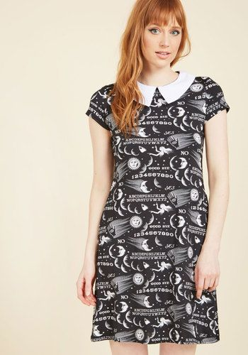 With how perfectly this black shift dress fits your quirky-cool aesthetic, it feels like you finding it was in the cards all along! A crisp white collar tops this pocketed frock, and continues its contrast motif through the sun, moon, and mysterious letter print atop its silky-smooth knit fabric. Pure magic!