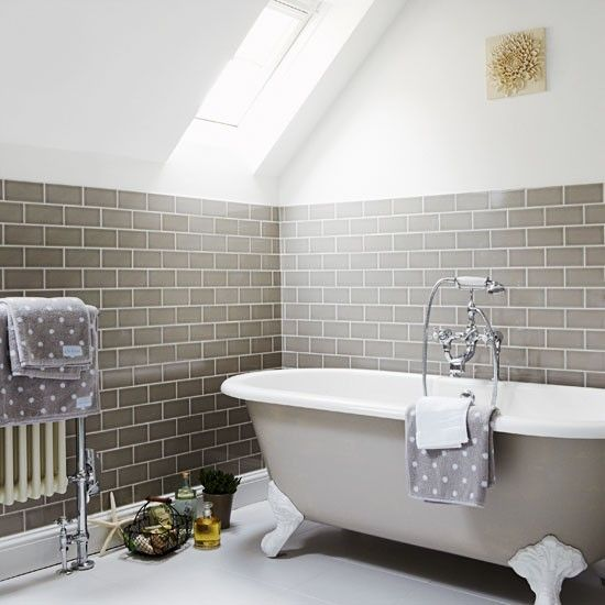 Attic bathroom This beautiful family bathroom has striking grey wall tiles that stop where the attic ceiling begins to slope upwards. The roll-top bath is painted in the same soft grey, with everything else in simple white.