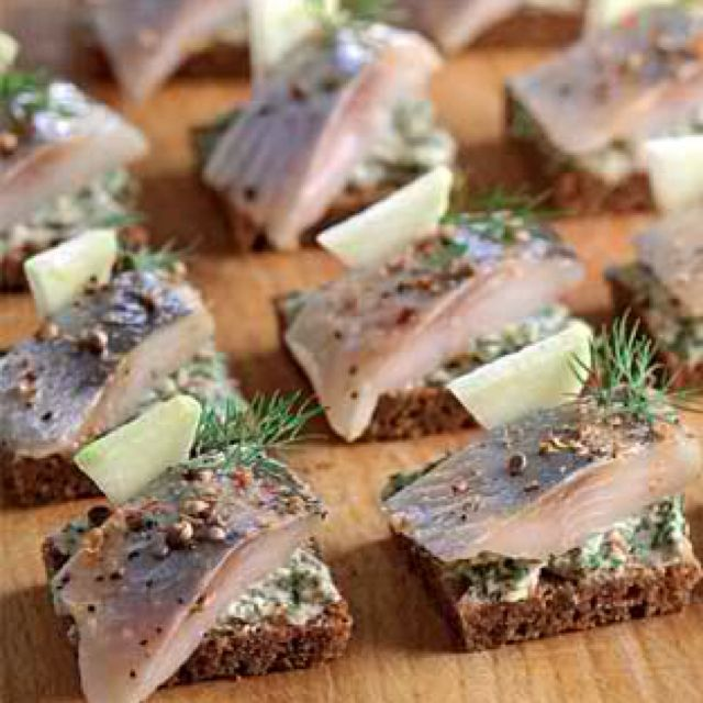 Russian style appetizers - herring on rye bread with butter and dill, perfect with a shot of vodka
