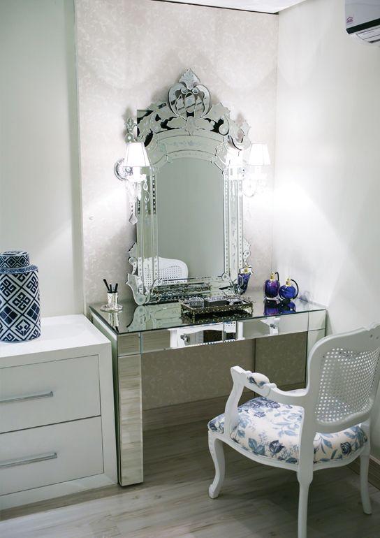 A penteadeira totalmente espelhada compõe com espelho veneziano e duas delicadas arandelas com pingentes de cristal.